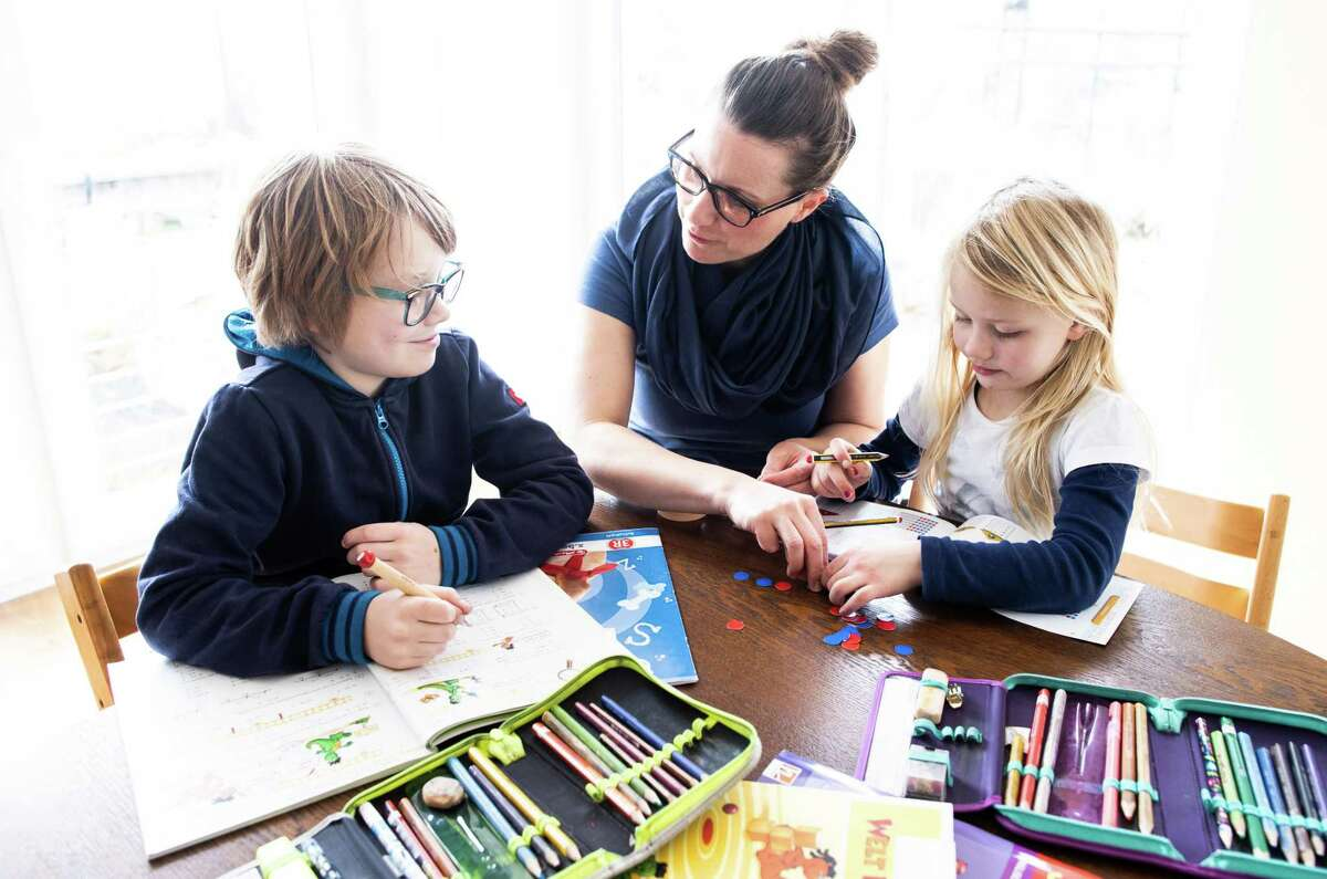 DINSLAKEN, GERMANY - MARCH 15: A mother helps her nine-year-old son and six-year-old daughter to do school homework on March 15, 2020 in Dinslaken, Germany. As the number of confirmed cases of coronavirus infection continues to rise daily across Germany so is the impact of the virus on everyday life.