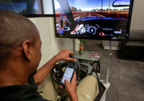 Damon Head, a technician with Comcast, struggles to text and drive a simulator during a demonstration of the dangers of texting and driving at Comcast's Houston office on Tuesday, April 30, 2019.