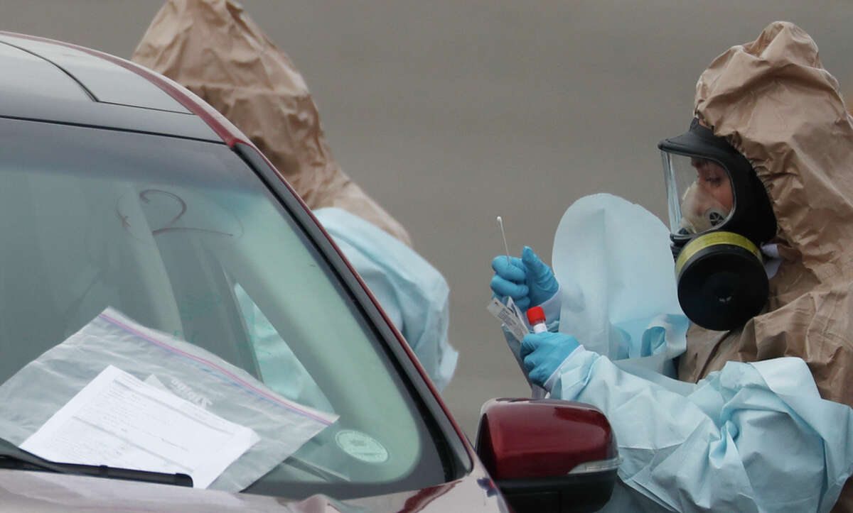 Colorado National Guard medical personnel perform coronavirus test on a motorist at a drive-through testing site outside the Denver Coliseum in Denver this month. The most extensive role for the military thus far is by the National Guard, which is being called up by governors in several states to provide a range of support.
