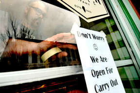Trevor Taynor of 222 Artisan Bakery and Cafe in Edwardsville hangs a sign on the front door of the business Monday afternoon, letting customers know that even though the dining room will be closed due to the threat of coronavirus spreading, the operation will still be open for takeout.