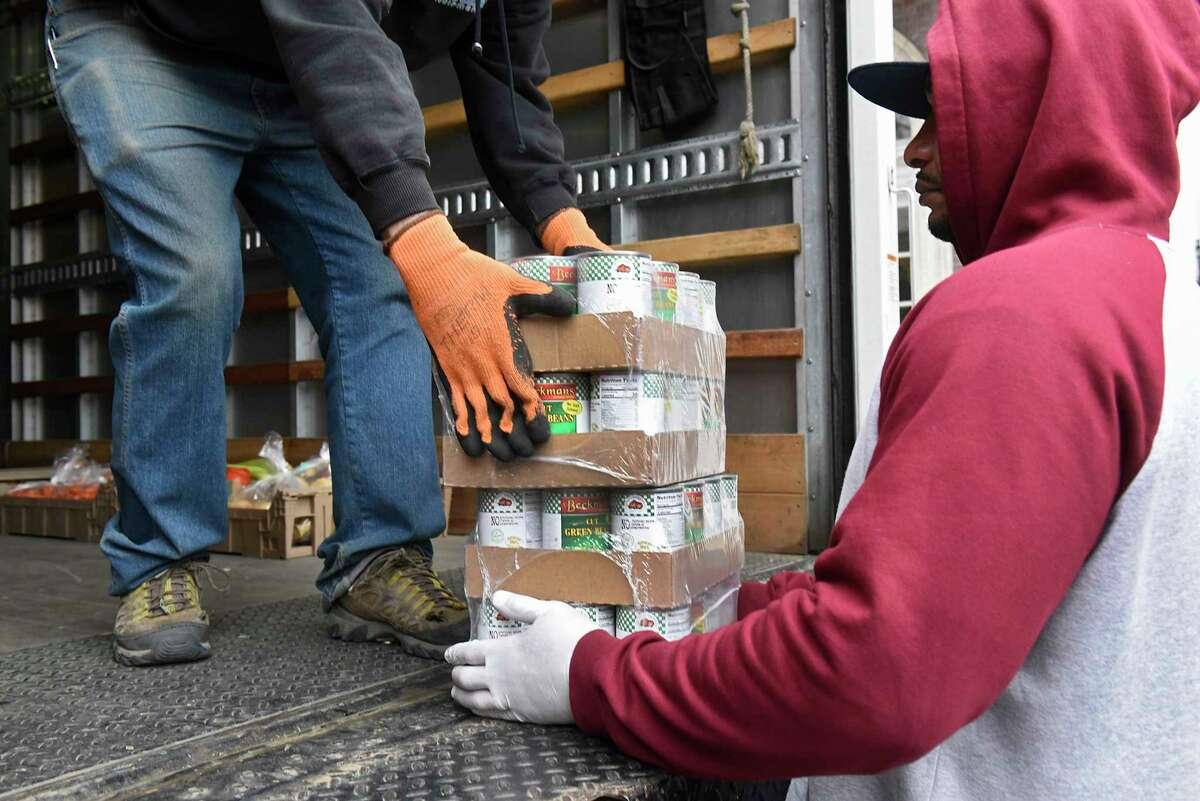 YWCA staff member Rick Rivera, right, helps bring in food to the YWCA delivered by Pete Borys, left, of the Food Pantries for the Capital District on Tuesday, March 17, 2020 in Troy, N.Y. (Lori Van Buren/Times Union)