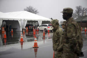 Members of the New York Army National Guard stand as vehicles enter a six lane COVID-19 drive-through testing facility at Glen Island Park in New Rochelle, New York, U.S., on Friday, March 13, 2020. President Donald Trump plans to declare a national emergency on Friday over the coronavirus outbreak, invoking the Stafford Act to open the door to more federal aid for states and municipalities, according to two people familiar with the matter. Photographer: Angus Mordant/Bloomberg
