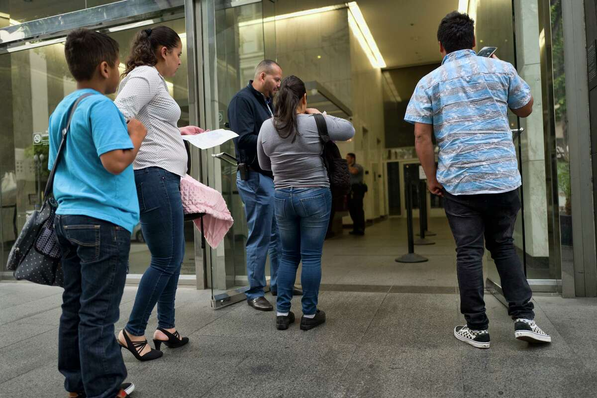In this May 30, 2019, file photo, immigrant families show paperwork to enter an immigration court in an office building in downtown Los Angeles.