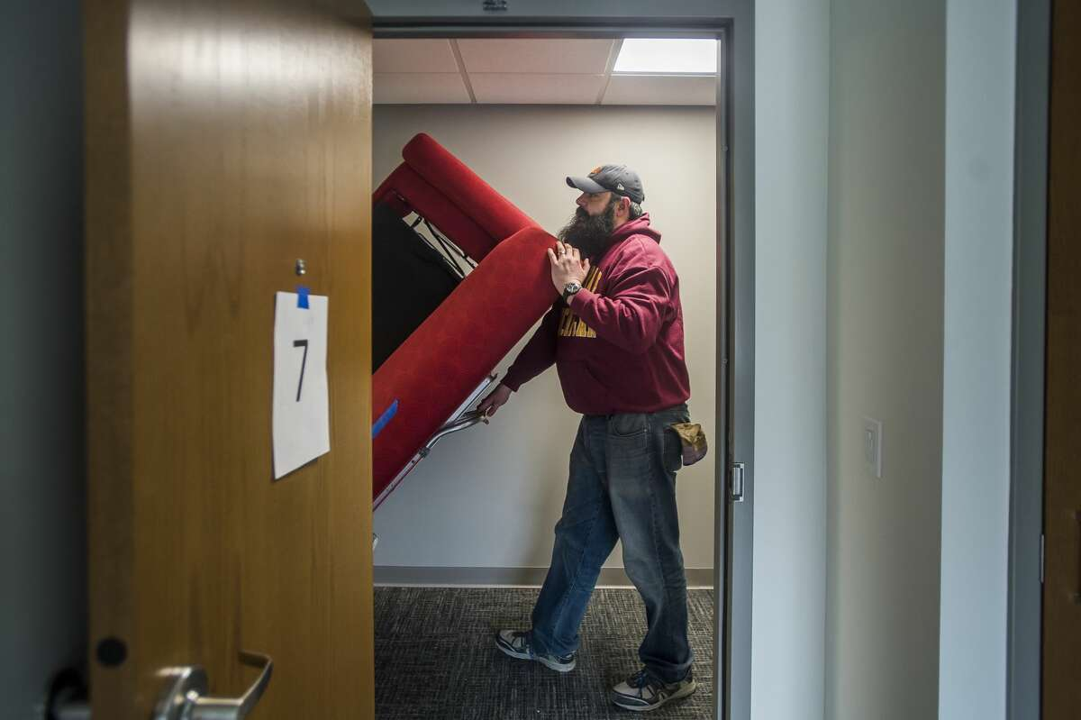 Chris Wakeman pushes a couch on a dolly as Shelterhouse staff move into their new location at 2500 Waldo Avenue Tuesday, March 17, 2020. Corrigan Moving Services offered their assistance in the moving process at no cost to Shelterhouse. (Katy Kildee/kkildee@mdn.net)