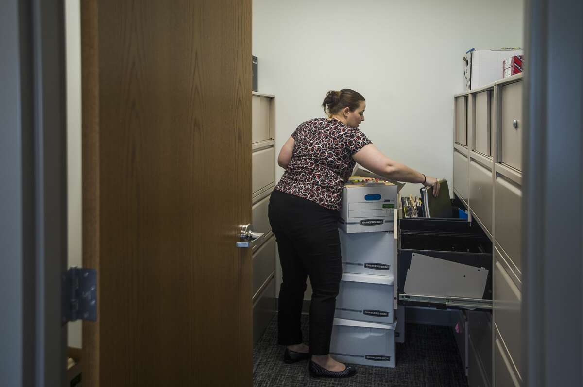 Savannah Louchart organizes files inside Shelterhouse's new location at 2500 Waldo Ave. Tuesday, March 17, 2020 in Midland. The previous, 90-year-old Shelterhouse facility contains six bedrooms and a total of 17 beds, requiring a communal living situation. The new location contains 48 beds across 15 suites, each designated for a single family. (Katy Kildee/kkildee@mdn.net)