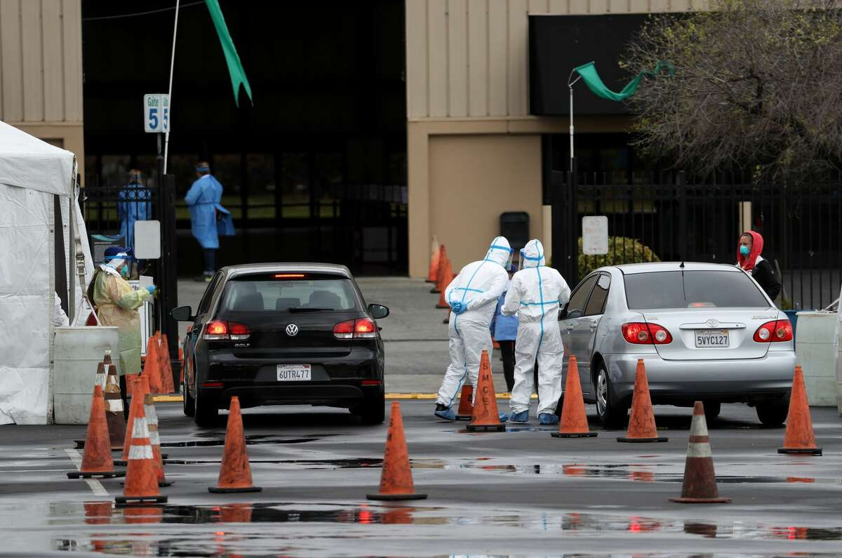 Medical personnel surround a car that is going through a coronavirus drive-thru test clinic at the San Mateo County Event Center.