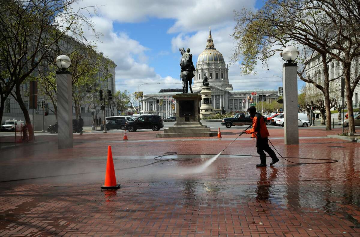 A worker power washes the sidewalk near San Francisco City Hall on March 16, 2020 in San Francisco, California. Public areas around the country are mostly empty as people around the country are staying away from from large gatherings in an attempt to slow the spread of COVID-19.
