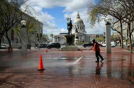 A worker power washes the sidewalk near San Francisco City Hall on March 16, 2020 in San Francisco, California. Public areas around the country are mostly empty as people around the country are staying away from from large gatherings in an attempt to slow the spread of COVID-19. (Photo by Justin Sullivan/Getty Images)