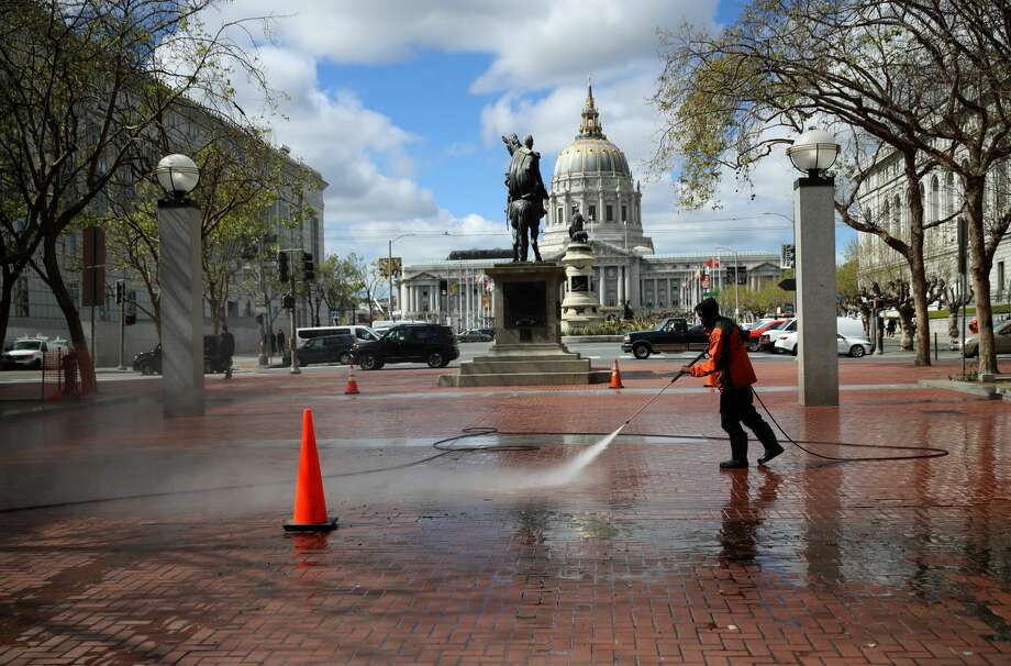 A worker power washes the sidewalk near San Francisco City Hall on March 16, 2020 in San Francisco, California. Public areas around the country are mostly empty as people around the country are staying away from from large gatherings in an attempt to slow the spread of COVID-19. Photo: Justin Sullivan/Getty Images