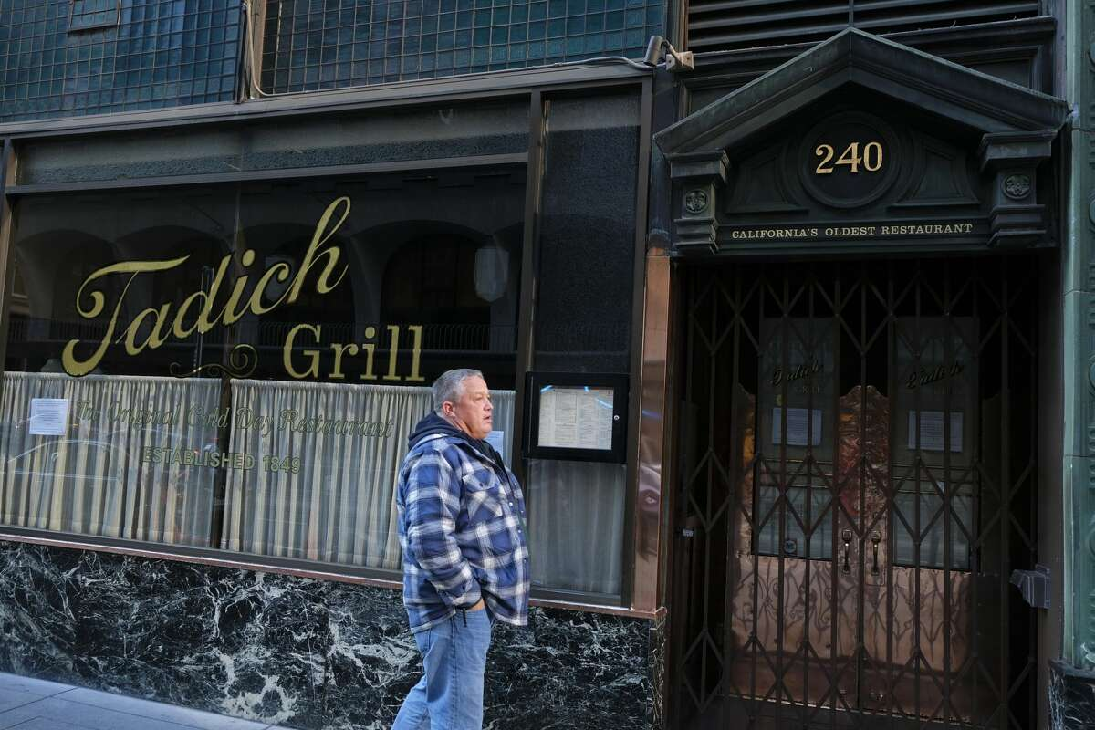 A man stands in front of the shuttered Tadich Grill in the Financial District and looks down California Street Monday, March 16, 2020, in San Francisco. Officials in seven San Francisco Bay Area counties have issued a shelter-in-place mandate affecting about 7 million people, including the city of San Francisco itself. The order says residents must stay inside and venture out only for necessities for three weeks starting Tuesday. It's the latest effort by officials to curb the spread of the novel coronavirus. The restaurant is California's oldest continually running restaurant dating to 1849.