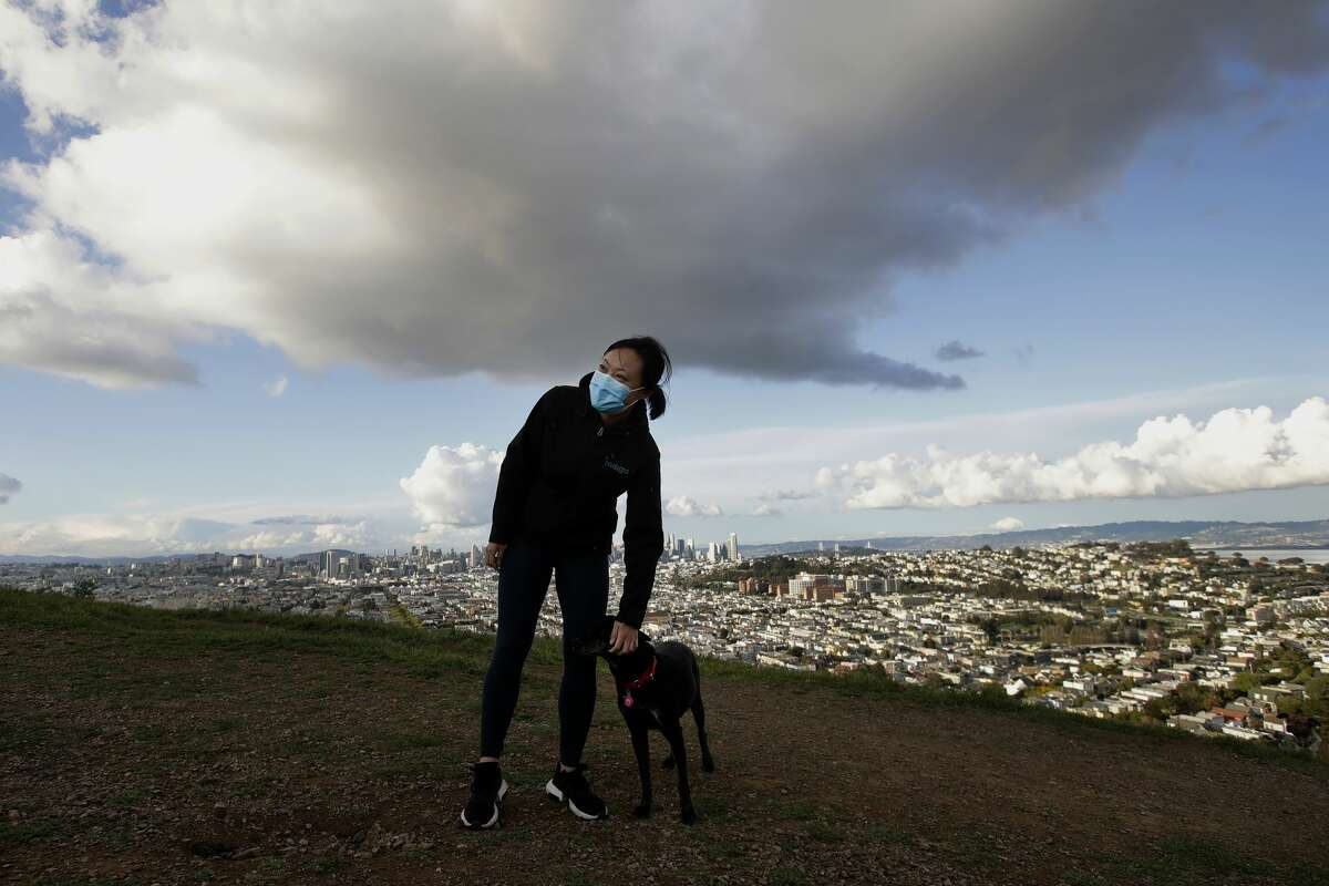 Lisa Wang wears a mask while walking her dog Rooney on Bernal Heights Hill in San Francisco, Monday, March 16, 2020. Officials in six San Francisco Bay Area counties issued a shelter-in-place mandate Monday affecting nearly 7 million people, including the city of San Francisco itself. The order says residents must stay inside and venture out only for necessities for three weeks starting Tuesday in a desperate attempt by officials to curb the spread of the novel coronavirus. (AP Photo/Jeff Chiu)