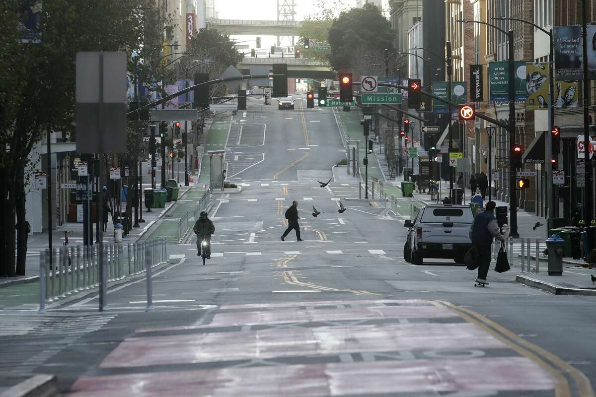 A man crosses a nearly empty street in San Francisco, Tuesday, March 17, 2020.