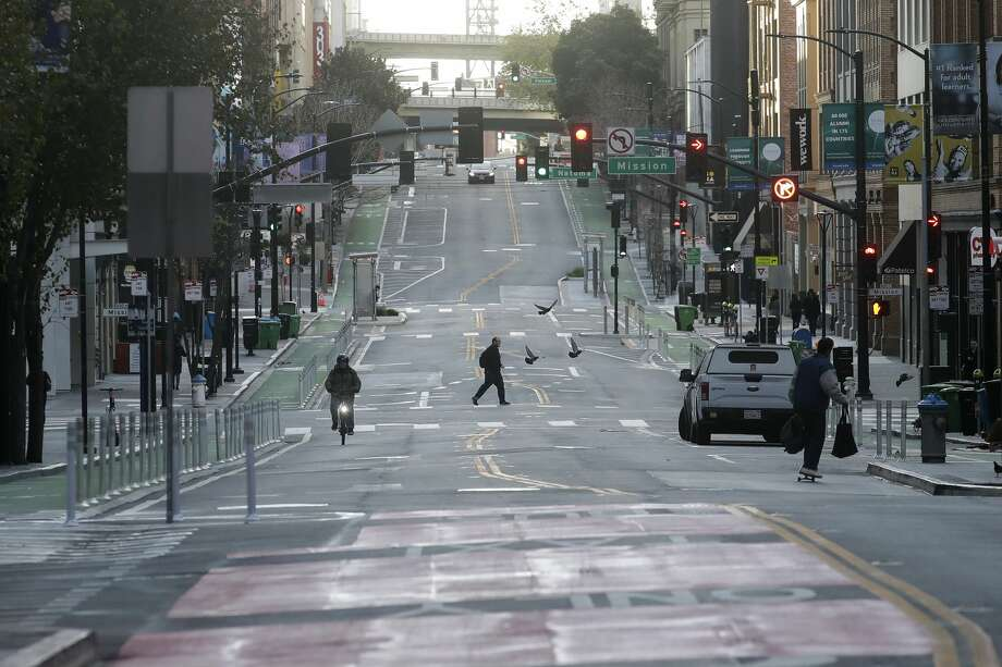 A man crosses a nearly empty street in San Francisco, Tuesday, March 17, 2020. Photo: Jeff Chiu/AP