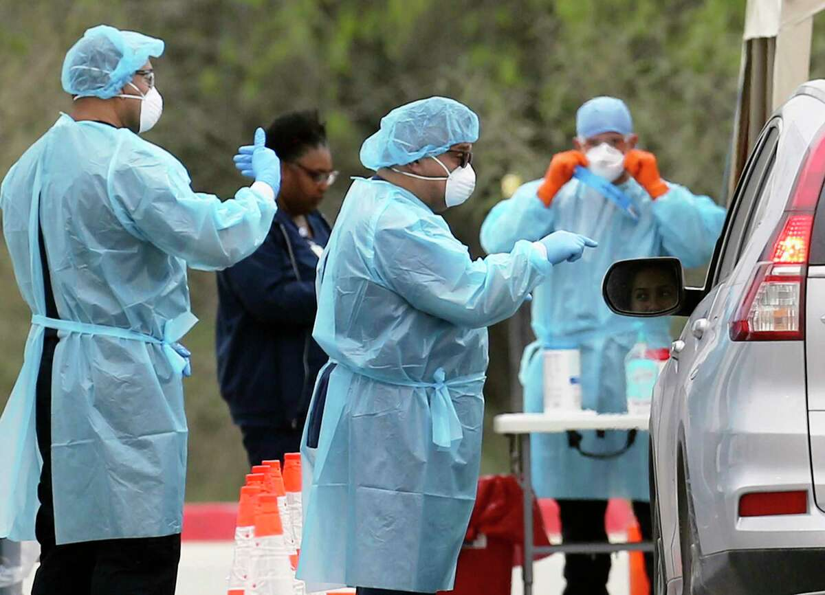 Medical personnel talk with an individual who arrived at the drive up screening center in the Medical Center area for people who may be infected with the coronavirus to be tested on Monday, Mar. 16, 2020. Testing continues across the county, officials said. Two new pop-up sites with free testing will be available Friday and Saturday, 10 a.m.-2 p.m. at Blossom Athletic Center, 12002 Jones Maltsberger Road, and Somerset Elementary, 7840 6th St. No appointment is required and you don't need to have any symptoms.