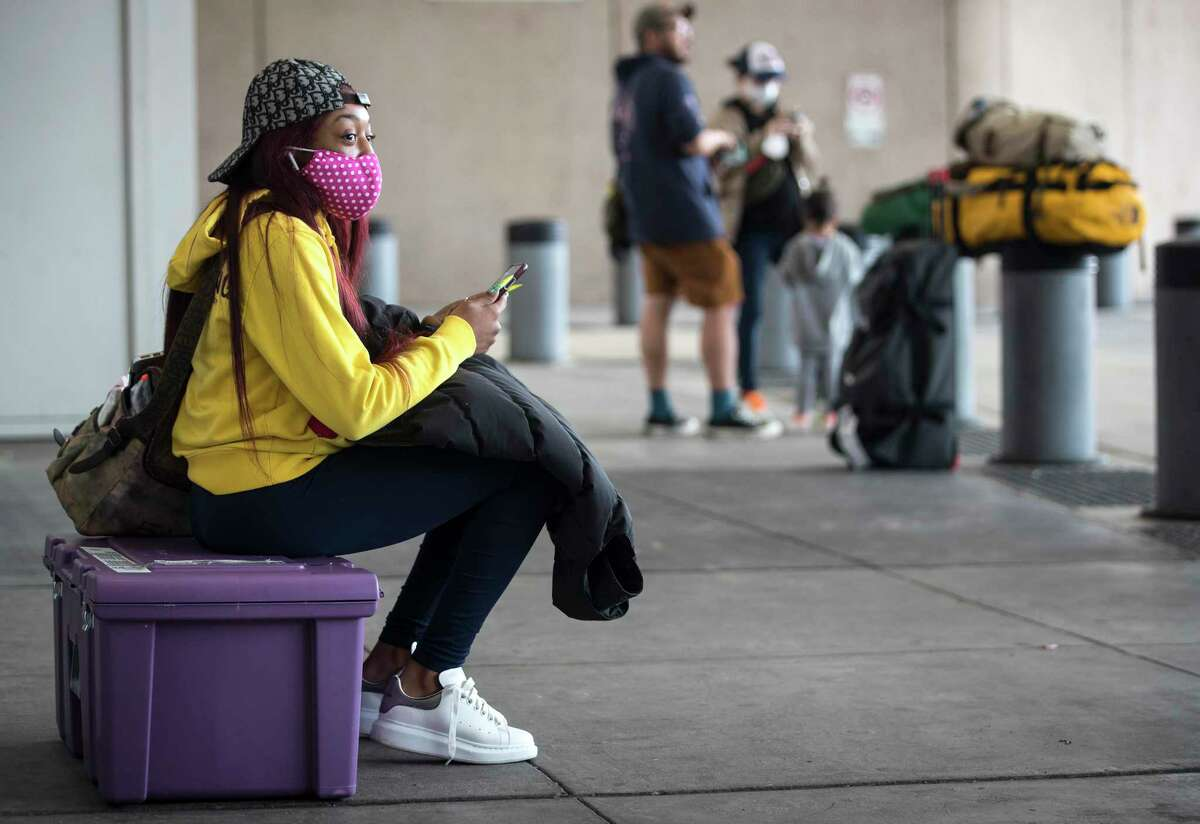 Terri Thomas sits on her luggage while waiting on her rideshare on Tuesday, March 17, 2020 outside Terminal C at George Bush Intercontinental Airport in Houston. Thomas arrived home in Houston from New York, where she thought she was going to be stranded as restrictions due to COVID-19 continue to grow.