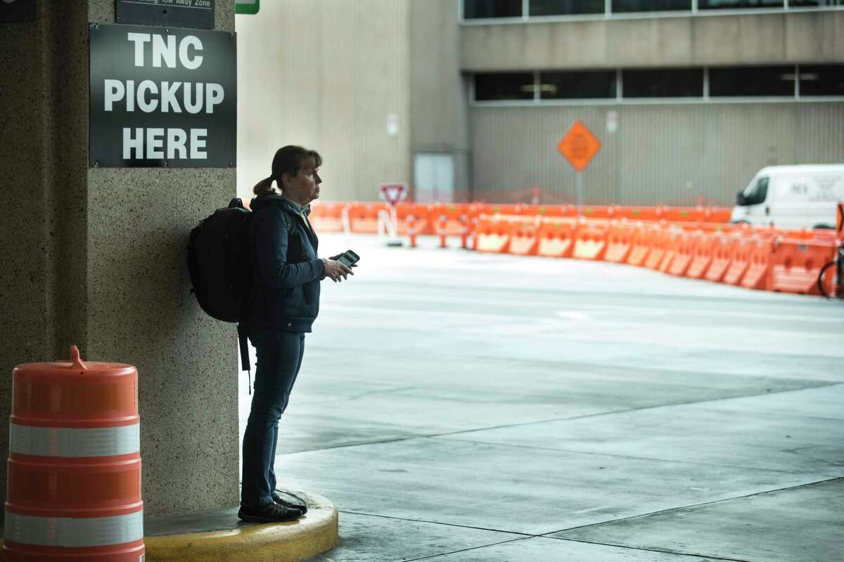 A passenger stands on a curb while waiting on her rideshare on Tuesday, March 17, 2020 at George Bush Intercontinental Airport in Houston.
