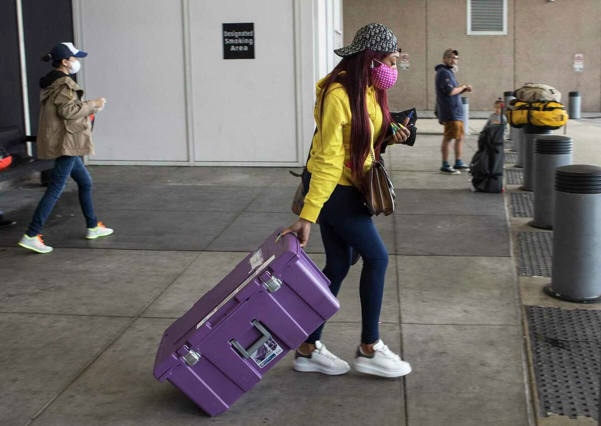 Terri Thomas walks to her rideshare on Tuesday, March 17, 2020 outside the Terminal C at George Bush Intercontinental Airport in Houston. Thomas arrived home in Houston from New York, where she thought she was going to be stranded as restrictions due to COVID-19 continue to grow.