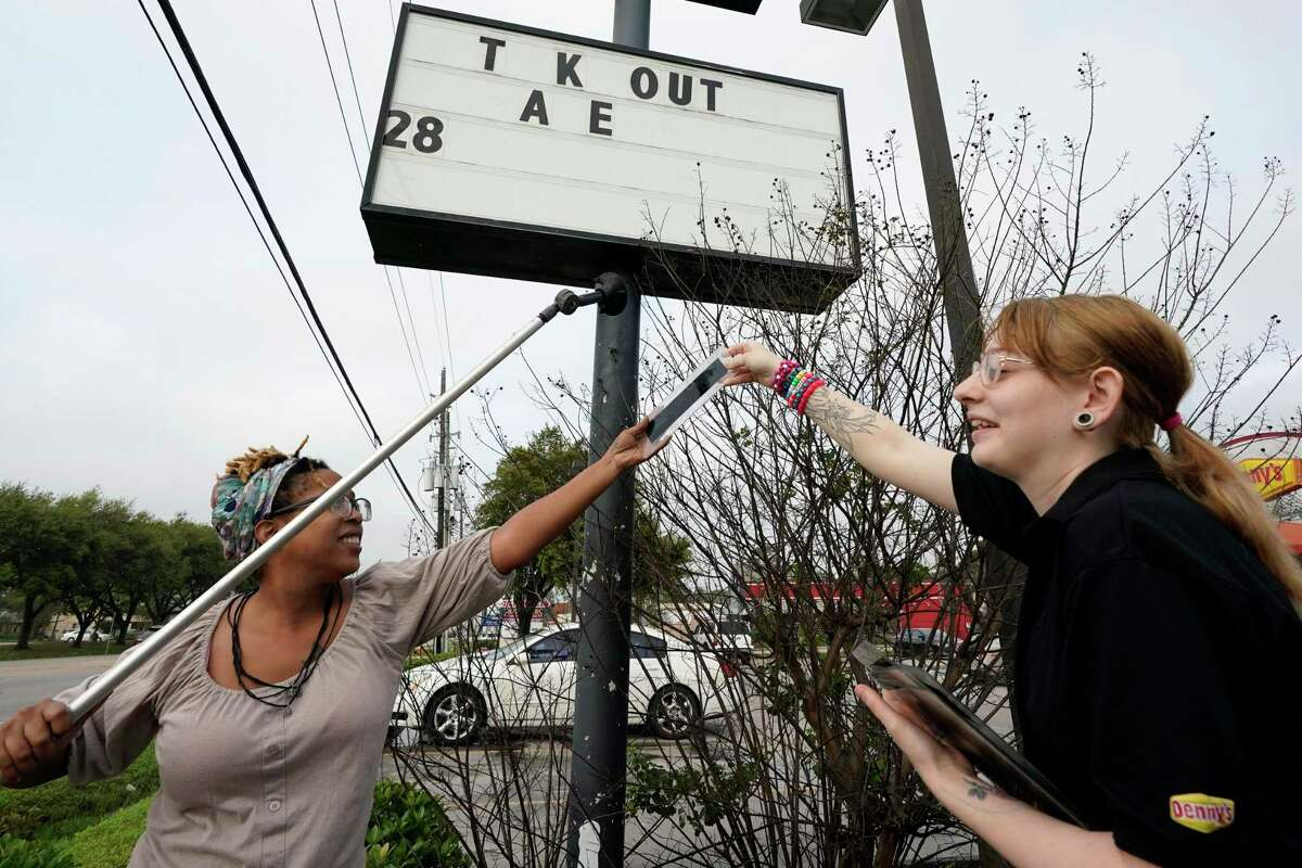 Ieisha Dede, left, and Cali Malatek put up a take out sign outside a Denny's restaurant Tuesday, March 17, 2020, in Spring, Texas. Houston area bars and restaurants have been ordered to follow new restrictions for the next 15 days in an effort to curb coronavirus exposure. Bars and nightclubs must close and restaurants can only be open for delivery, pickup and drive-thru services. No in-dining service is allowed. (AP Photo/David J. Phillip)