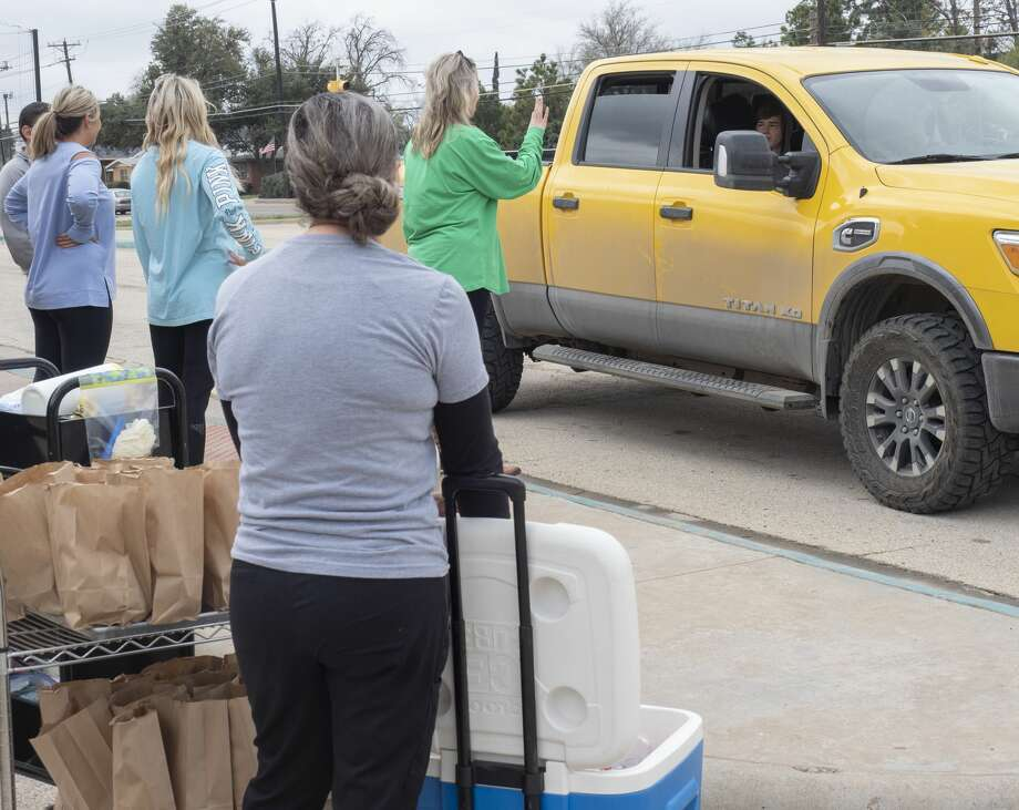San Jacinto staff deliver free lunches 03/17/2020 to students as parents drive up through the drop-off area off Garfield. Tim Fischer/Reporter-Telegram Photo: Tim Fischer/Midland Reporter-Telegram