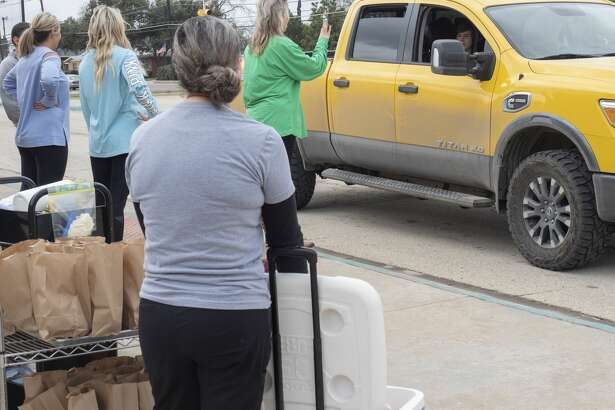San Jacinto staff deliver free lunches 03/17/2020 to students as parents drive up through the drop-off area off Garfield. Tim Fischer/Reporter-Telegram