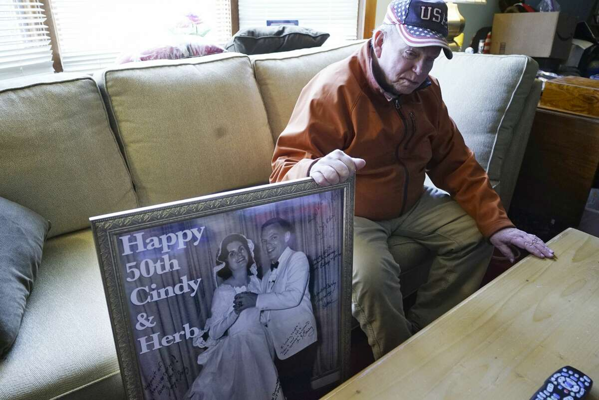 Herbert Sodher poses with a portrait of him and his wife, Cynthia. Sodher is unable to visit his wife in the Saratoga Springs hospice where she lives because of new visitation policies stemming from the coronavirus pandemic.