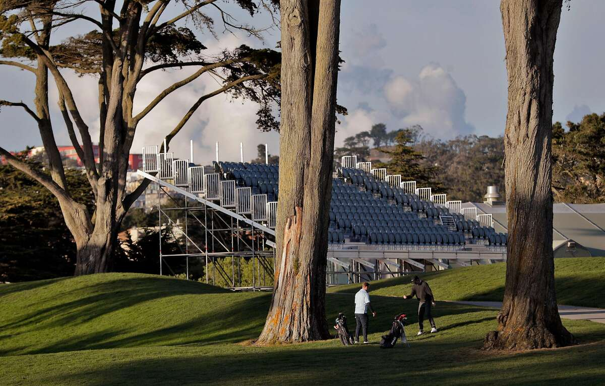 One golfer advises another in front of temporary seating under construction at TPC Harding Park where preparations are underway for the 2020 PGA Championship in San Francisco, Calif., on Monday, March 16, 2020.