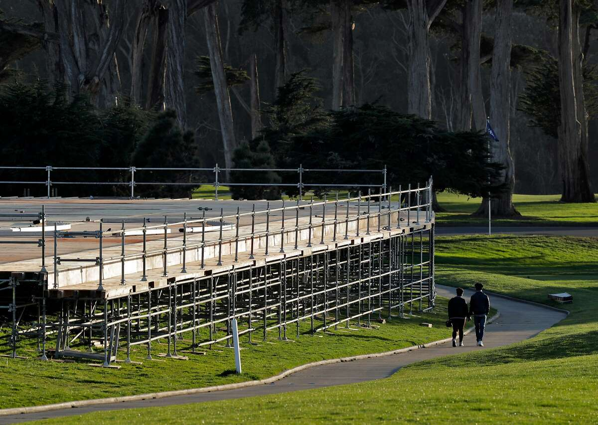 A couple walks by grandstands under construction at TPC Harding Park where preparations are underway for the 2020 PGA Championship in San Francisco, Calif., on Monday, March 16, 2020.
