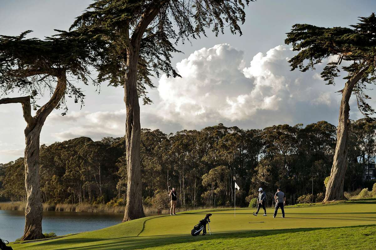 Darren Long, left, Saam Arzang, center, and and Arti Mansbach, right, finish off the 18th hole at TPC Harding Park where preparations are underway for the 2020 PGA Championship in San Francisco, Calif., on Monday, March 16, 2020.