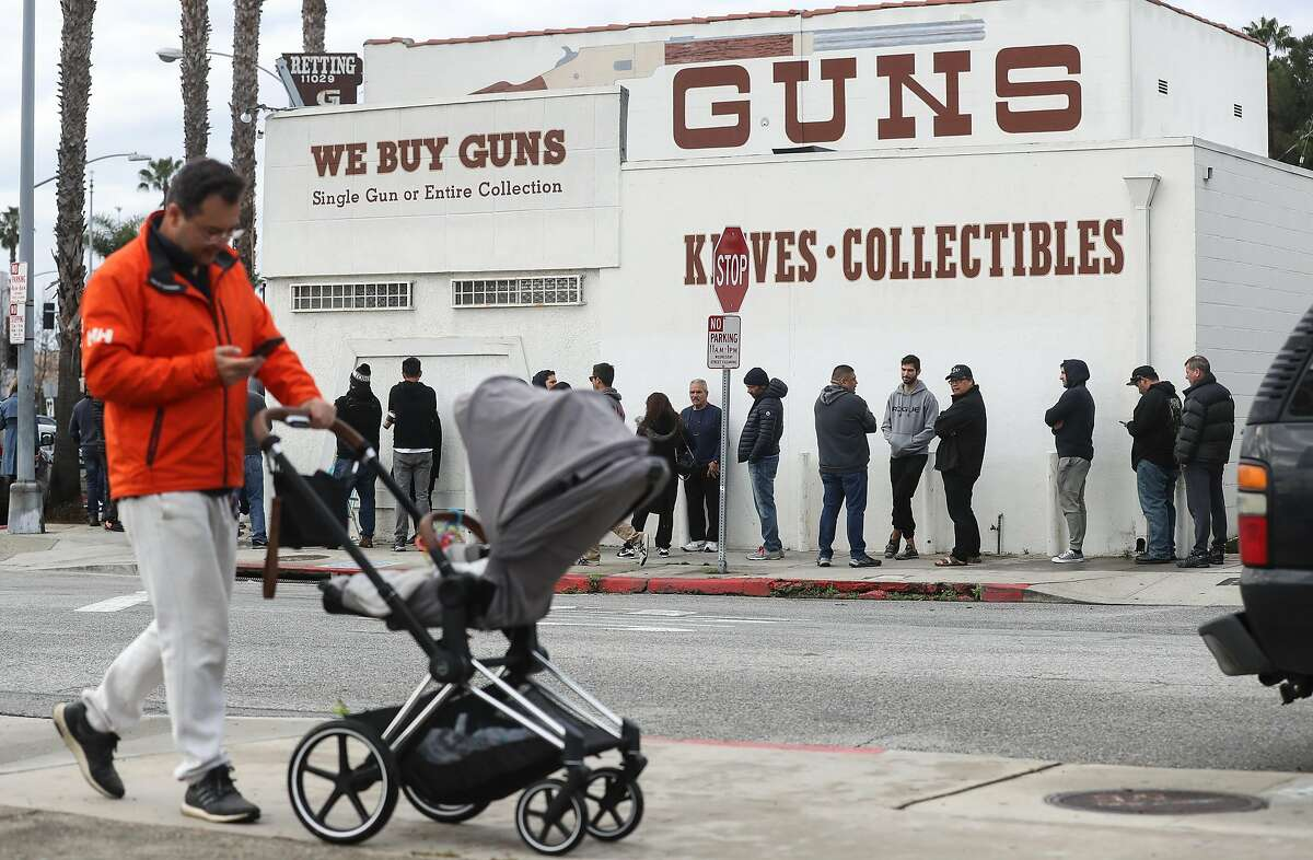 CULVER CITY, CALIFORNIA - MARCH 15: A man walks with a stroller as people stand in line outside the Martin B. Retting, Inc. guns store on March 15, 2020 in Culver City, California. The spread of Coronavirus (COVID-19) has prompted some Americans to line up for supplies in a variety of stores. (Photo by Mario Tama/Getty Images) *** BESTPIX ***