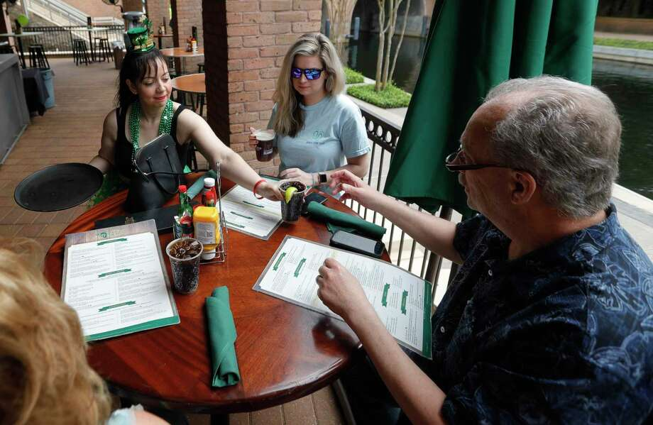 Waitress Gabby Garcia, hands Phil Luce, from Michigan, a drink as he dines with his daughter, Crystal Stanley, and wife, Kathy, at The Goose's Acre, Tuesday, March 17, 2020, in The Woodlands. The Luces came from Michigan for the week to visit their daughter when Montgomery County implemented new guidelines for restaurants and bars to reduce occupancy of the establishments to no more than 50 people, and tables are to be spaced a minimum of 10 feet apart. Photo: Jason Fochtman, Houston Chronicle / Staff Photographer / Houston Chronicle  © 2020