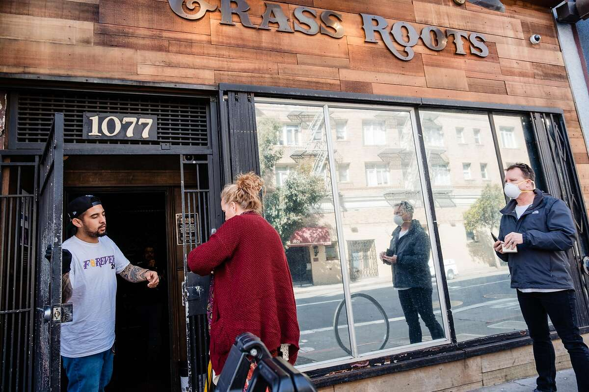 Customers line up in front of Grass Roots dispensary on Post Street in San Francisco, Calif. onTuesday, March 17, 2020.