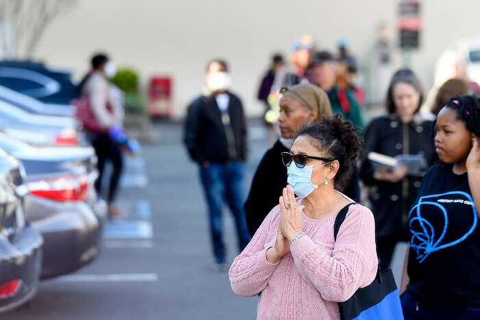 Angela Massella waits in line to buy supplies at Trader Joe's in Oakland, Calif., on Tuesday, March 17, 2020. Massella hoped to buy eggs, milk and paper towels as Alameda County entered its first day of shelter in place orders to slow the spread of coronavirus.