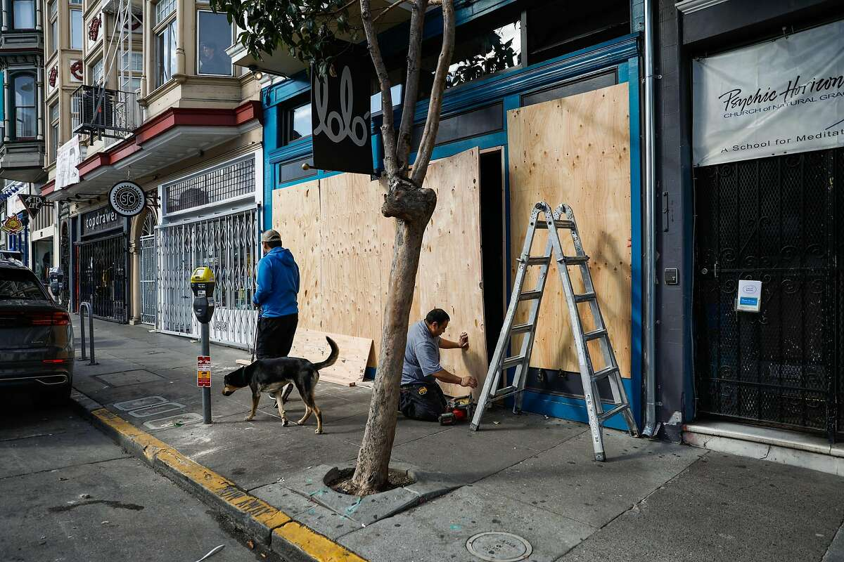 Robert Martinez (right) boards up Lolo restaurant out of fear of break-ins during the citywide lockdown on Valencia Street on Tuesday, March 17, 2020 in San Francisco, California.