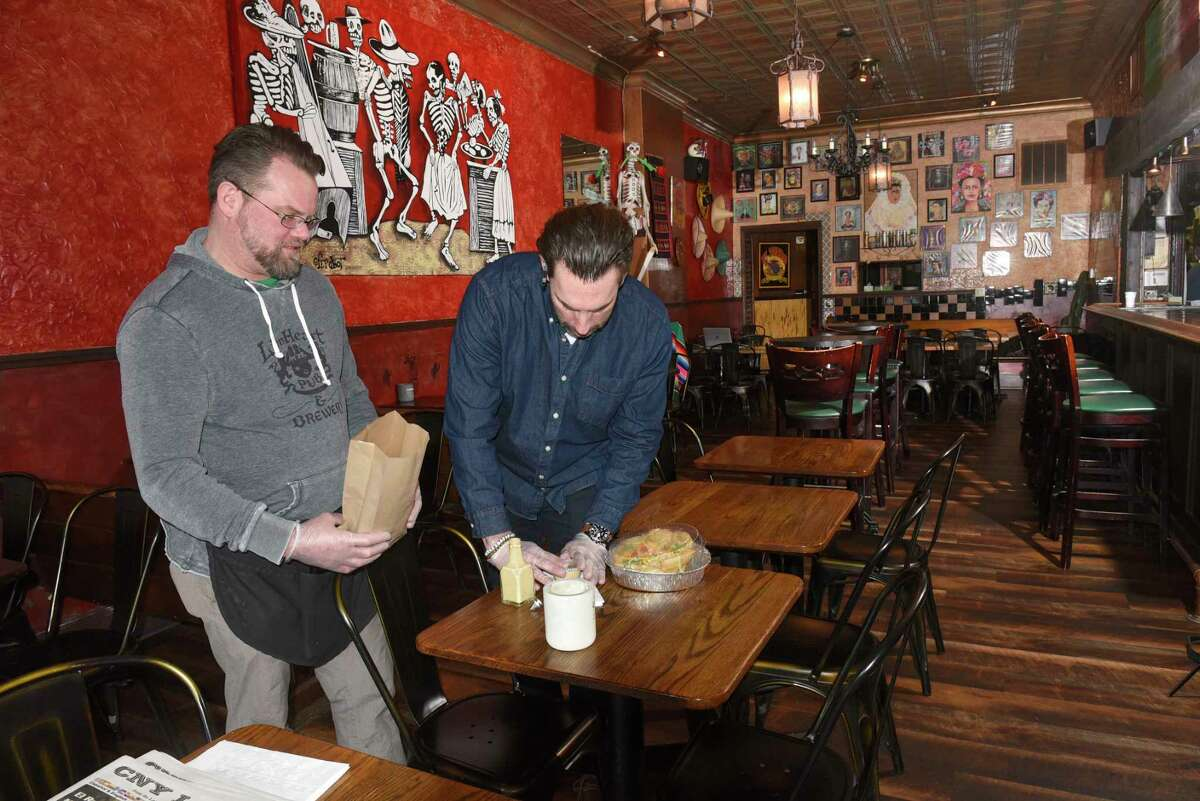 Bartender Richard Kuhn and owner Patrick Noonan pack up a to-go order in an empty El Loco restaurant on Tuesday, March 17, 2020 in Albany, N.Y. Because of the coronavirus restaurants are only able to do take-out orders at this time. (Lori Van Buren/Times Union)