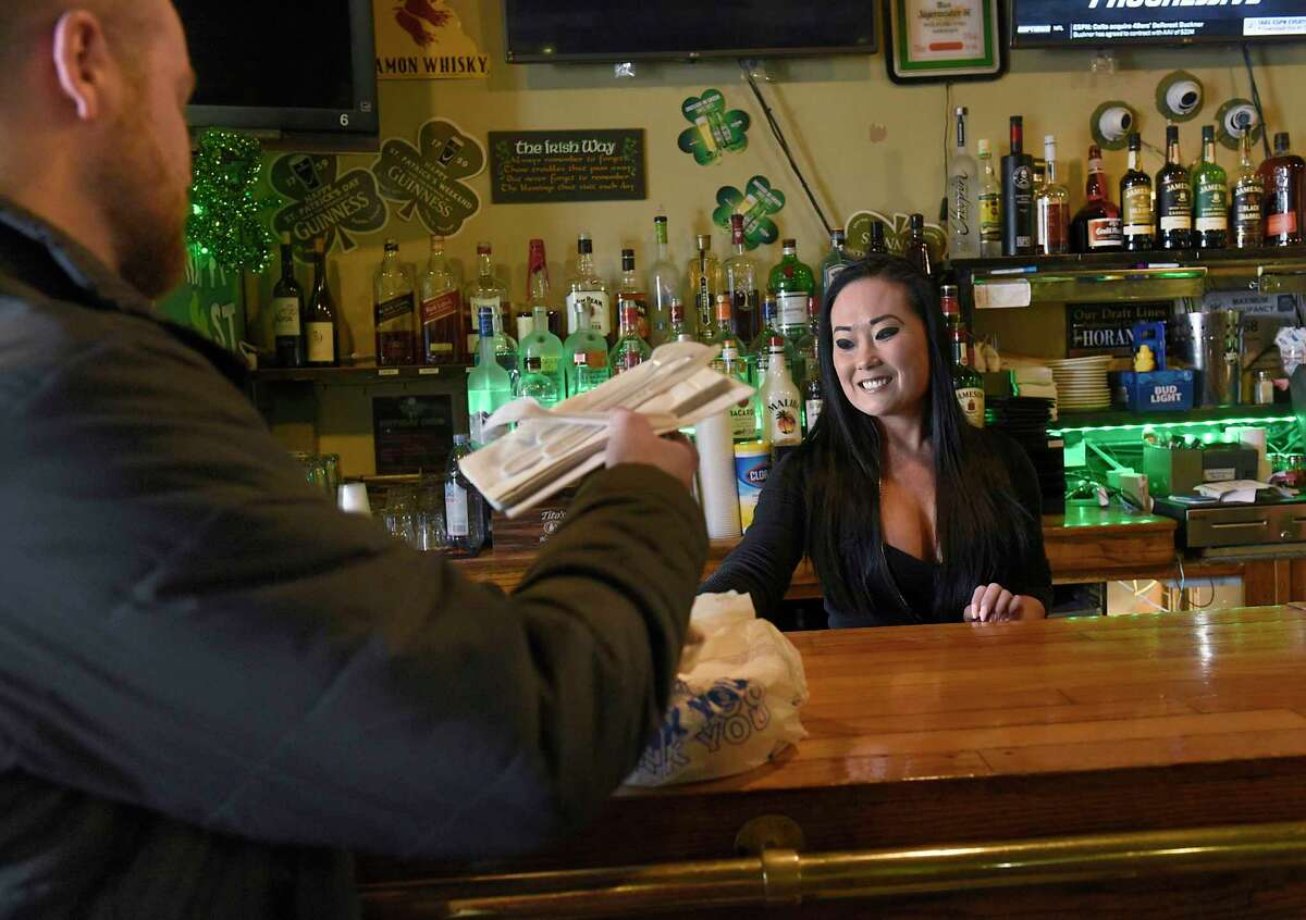 Adria Capuano, right, gives a customer his take-out order of corned beef and cabbage at Graney's Bar & Grill is empty on Tuesday, March 17, 2020 in Albany, N.Y. Because of the coronavirus restaurants are only able to do take-out orders at this time. (Lori Van Buren/Times Union)