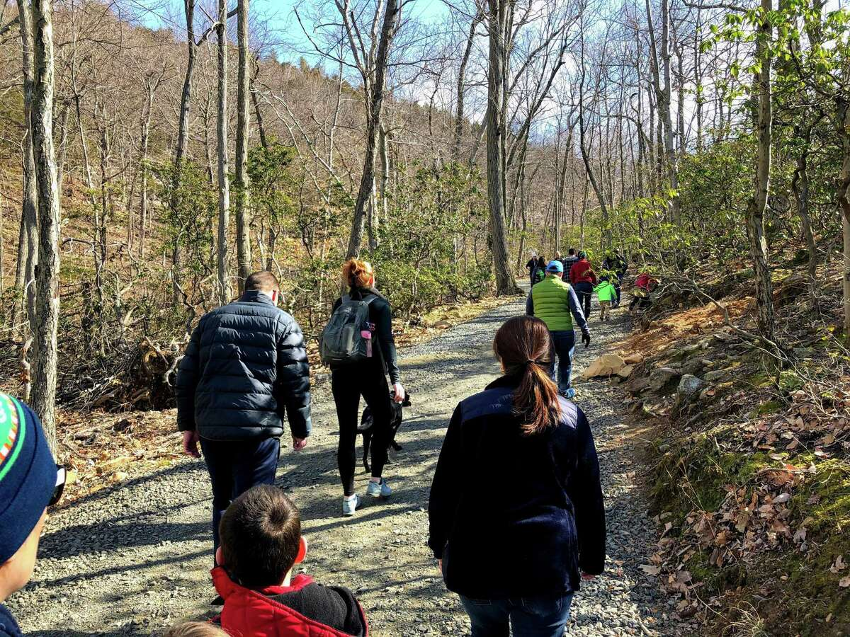 FILE PHOTO: Visitors keep a distance from each other on a sunny day going up the tower trail at Sleeping Giant State Park.