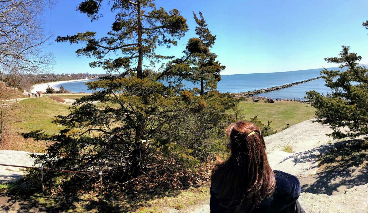 A woman enjoys the view from the rock ledge at Rocky Neck State Park.