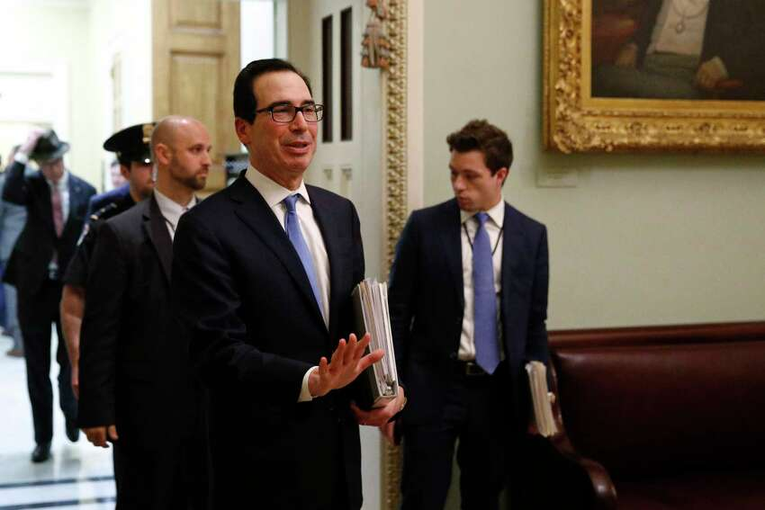 Treasury Secretary Steve Mnuchin asks members of the media to practice social distancing as he departs a meeting on Capitol Hill in Washington, Monday, March 16, 2020. Mnuchin met with with Senate Republicans on an economic lifeline for Americans affected by the coronavirus outbreak.