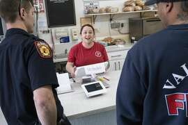 Vallejo Fire Department firefighters Kevin Brown, left, and Capt. Jason Ward, right talk to manager Erica Bostian, center, while picking up lunch at Picnicky's Sandwich Shop in Vallejo, Calif. on Tuesday, March 17, 2020. The firefighter union said members will forgo cooking in the firehouses to support local businesses affected by the downturn in business amid coronavirus concerns.