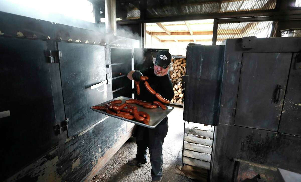 Russell Roegels, owner of Roegels Barbecue Co. at 2223 S. Voss pulls sausages out of the smoker. Roegels is among the Houston restaurant owners who are grappling with ways to stay in business since Harris Country enters 15-days of limiting service to only take-out and pick-up.