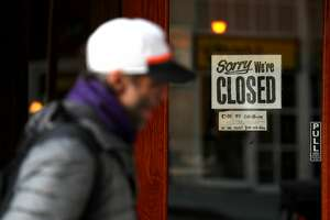 SAN FRANCISCO, CALIFORNIA - MARCH 17: A pedestrian walks by a closed sign on the door of a restaurant on March 17, 2020 in San Francisco, California. Seven San Francisco Bay Area counties have ordered residents to shelter in place in an effort to reduce social interaction and slow the spread of COVID-19. (Photo by Justin Sullivan/Getty Images)