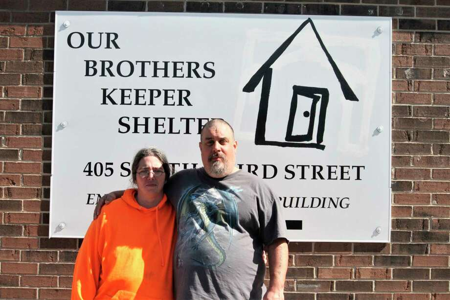 Our Brothers Keeper guest Brian Hudson poses with his fiancee outside of the shelter. Hudson said he's thankful OBK opted to remain open 24/7 in light coronavirus concerns because it gives him and his friends and family a warm place to stay during the day while other public buildings are closing. (Pioneer photo/Catherine Sweeney)