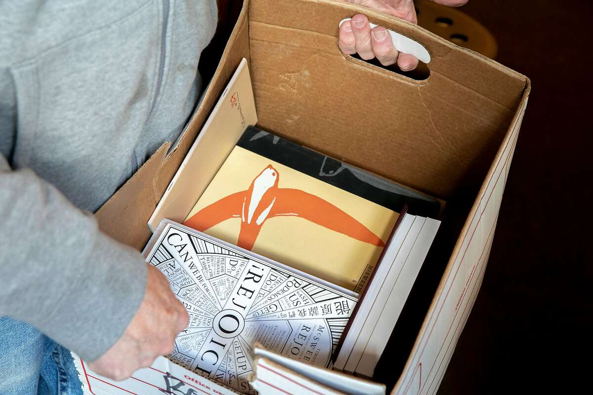Eric Whittington with a box of books requested by customers at Bird & Beckett Books & Records, Tuesday, March 17, 2020, in San Francisco, Calif. Whittington is the owner of the store, located at 653 Chenery St.