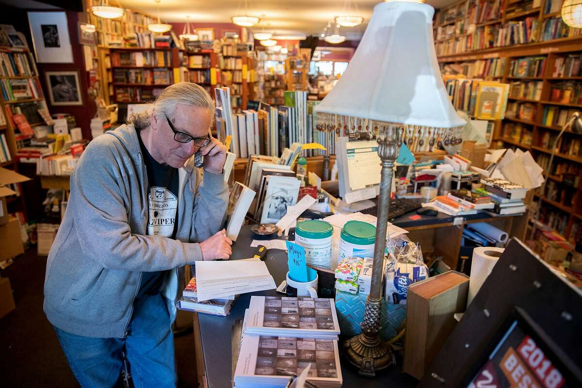 Eric Whittington takes a phone call from a customer for a book request at Bird & Beckett Books & Records, Tuesday, March 17, 2020, in San Francisco, Calif. Whittington is the owner of the store, located at 653 Chenery St. He lives in the same building as the bookstore, so is hunkering down in the shop to keep up with online sales and do curbside deliveries.
