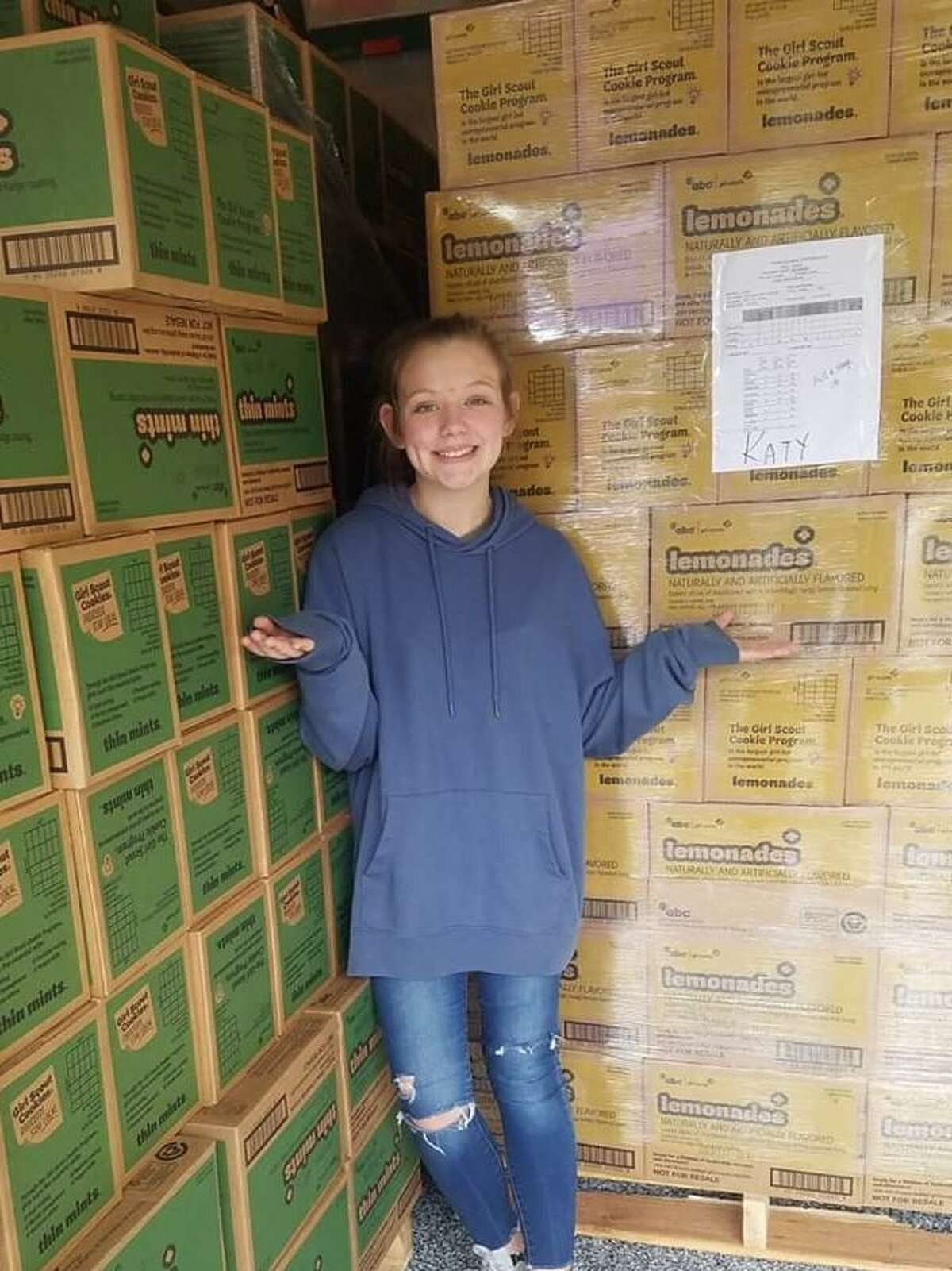 KayLee Belle Sullivan poses with boxes of cookies at her Girl Scout troop's cookie cupboard.