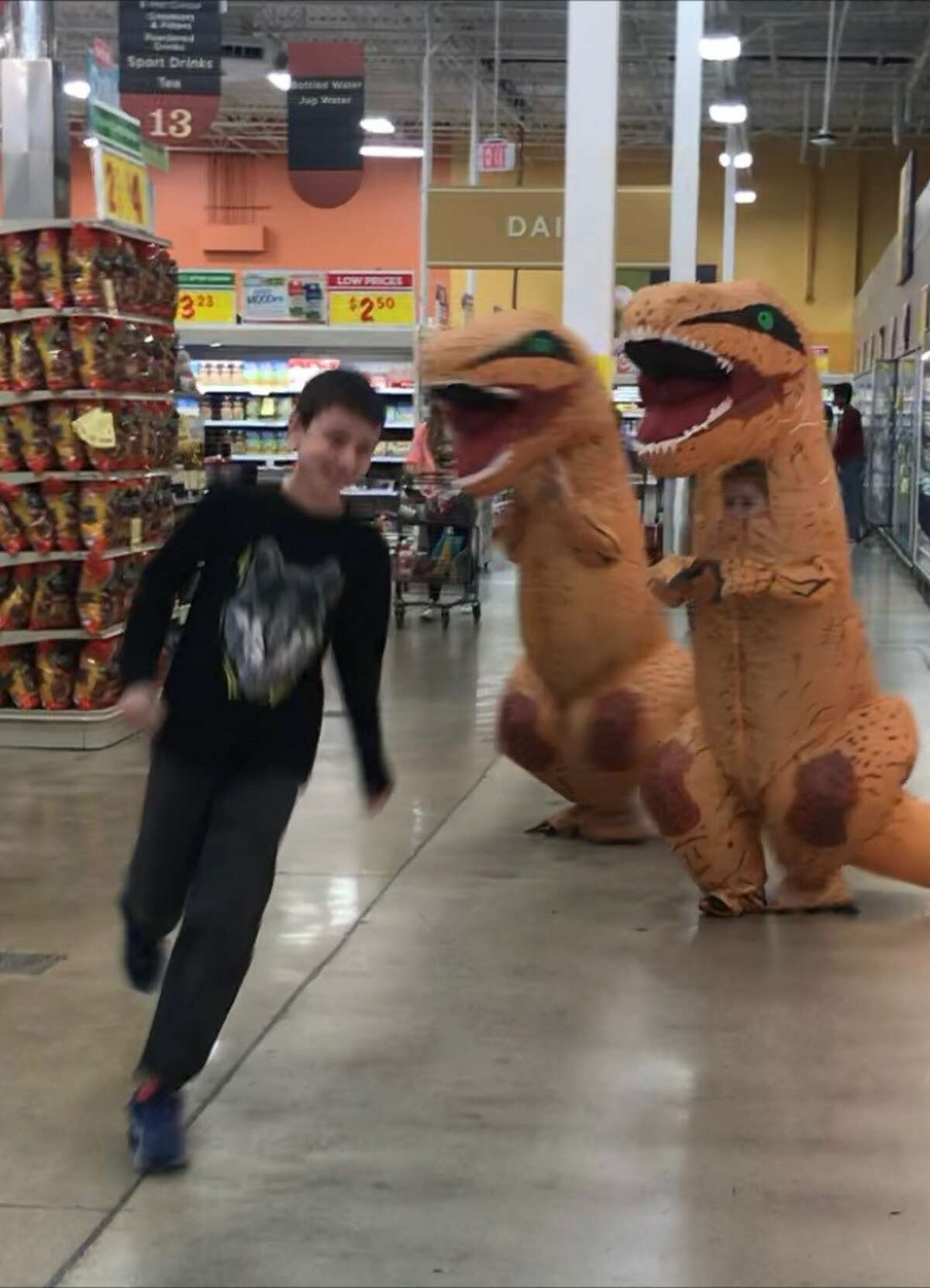 A San Antonio mom and her kids brought a bit of comic relief to their local H-E-B by shopping in dinosaur costumes.