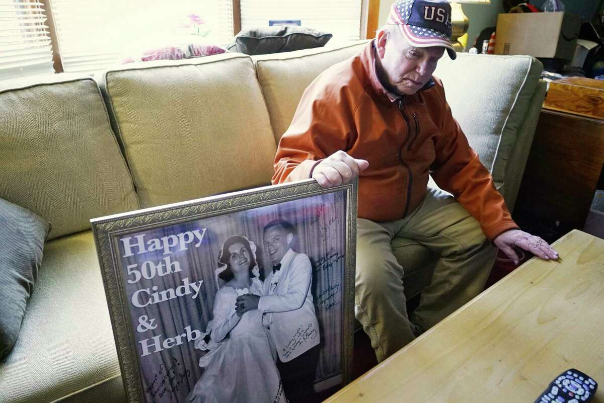 Herbert Sodher sits in his living room on Tuesday, March 17, 2020, in Saratoga Springs, N.Y. next to a large photo of he and his wife Cynthia on their wedding day given to them on their 50th wedding anniversary. Cynthia is an Alzheimer's patient in hospice in Saratoga Springs and Herbert is unable to visit her because of new rules at the hospice that limit visitations to cases only when the patient is close to death. (Paul Buckowski/Times Union)