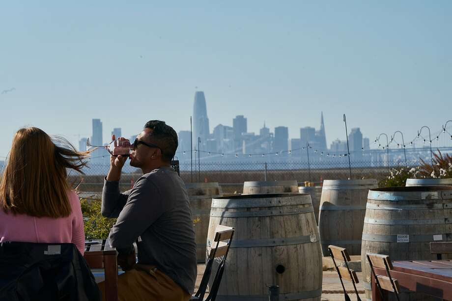 In February, before California tasting rooms were ordered to close, Ashley Chandler and Varun Sundar enjoyed a wine tasting at Urban Legend Cellars in Alameda. The winery is now offering complimentary shipping. Photo: Paul Kuroda / Special To The Chronicle