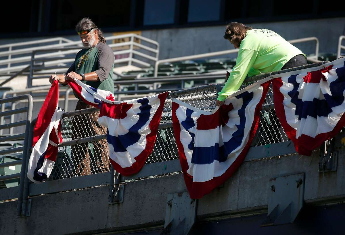 Stadium employees tie postseason bunting to a railing at the Coliseum in Oakland.