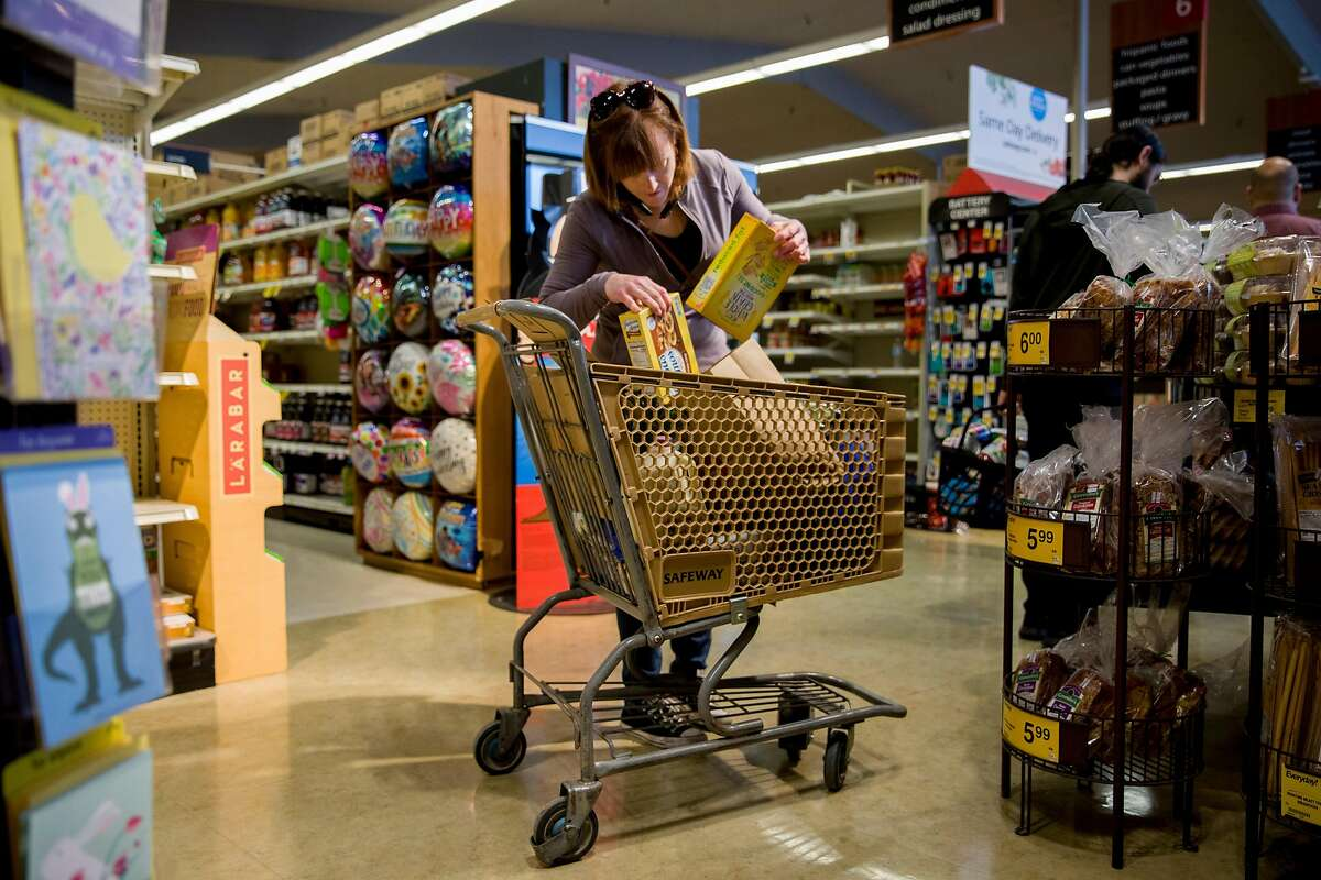 Grocery delivery shopper Courtney Fox of Newark begins bagging items as she stands in the checkout line while purchases groceries for three separate Instacart orders at Safeway in Palo Alto, Calif. Tuesday, March 17, 2020. As a shopper for Instacart, Courtney Fox finds herself on the front lines of keeping homebound Bay Area people supplied with food and essentials during the threat of the Coronavirus and shelter-in-place order was given to six Bay Area counties on Monday, March 16.